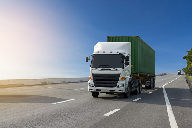 White Truck on highway road with green  container, transportation concept.,import,export logistic industrial Transporting Land transport on the asphalt expressway with blue sky